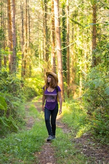 Traveler woman wearing a hat and looking at the forest pines