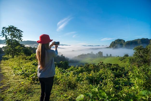 スマートフォンを使用して帽子をかぶった旅行者の女性は、霧の海で美しい山の風景を撮影します。