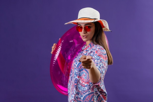 Traveler woman wearing summer hat and red sunglasses holding inflatable ring pointing with index finger with serious and confident facial expression standing on purple