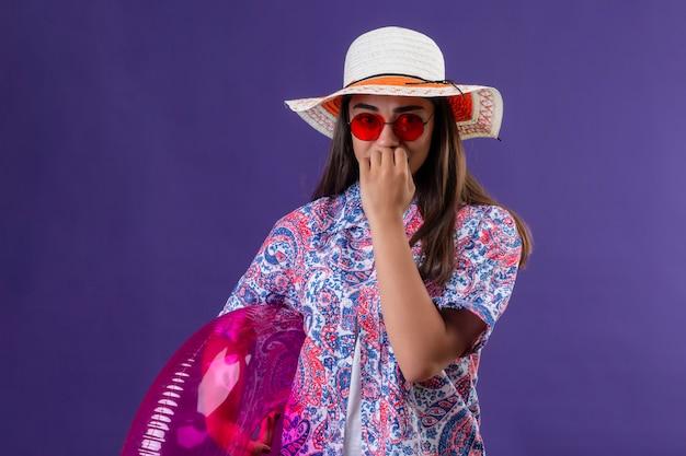 Donna viaggiatore che indossa cappello estivo e occhiali da sole rossi che tiene anello gonfiabile stressato e nervoso che si morde le unghie in piedi sulla porpora
