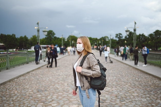 Путешественница с рюкзаком и медицинской маской