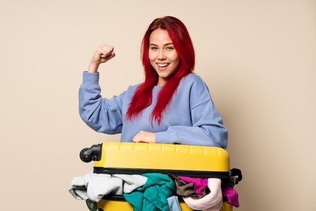 勝利を祝っているベージュの壁に分離された服の完全なスーツケースを持つ旅行者女性