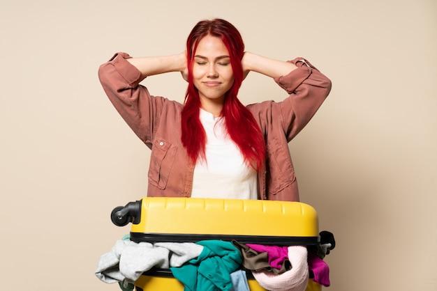 Путешественница с чемоданом, полным одежды, изолирована на бежевой стене и расстроена ушами