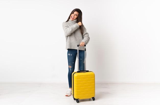 勝利を祝っている白い壁にスーツケースを持った旅行者女性