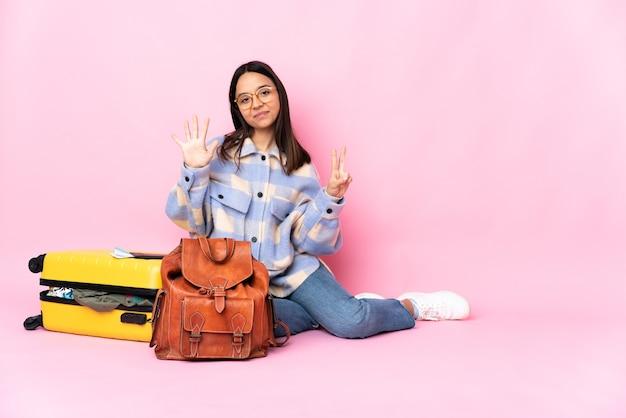指で7を数える床に座っているスーツケースを持つ旅行者の女性