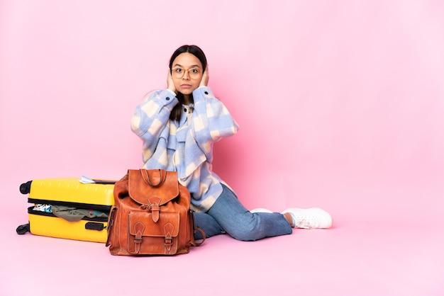 Женщина-путешественница с чемоданом сидит на полу в разочаровании и закрывает уши