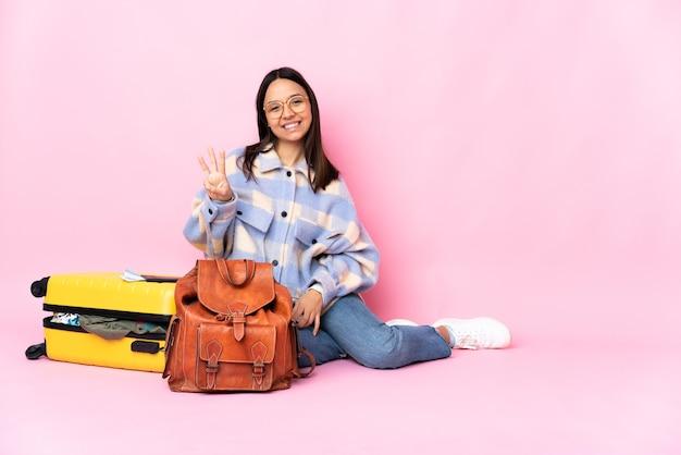 幸せな床に座って、指で3を数えるスーツケースを持つ旅行者の女性