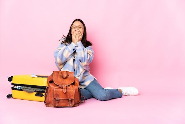Женщина-путешественница с чемоданом сидит на полу, счастливая и улыбается, прикрывая рот руками