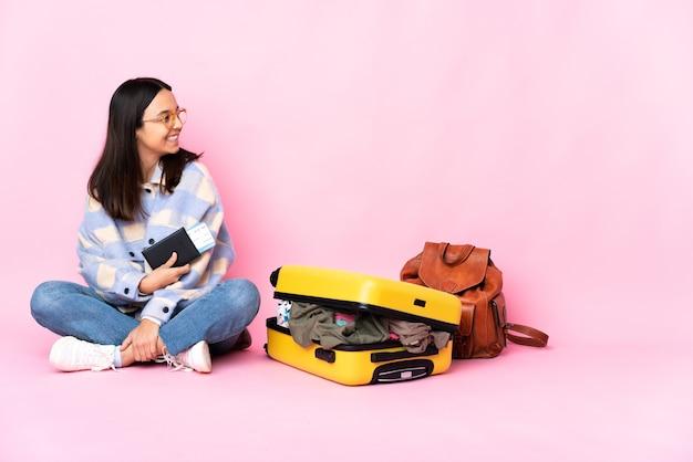 幸せと笑顔で床に座っているスーツケースを持つ旅行者の女性