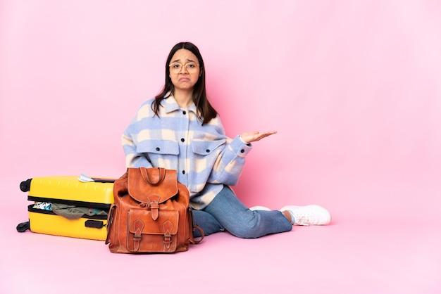 의심을 갖는 바닥에 앉아 가방을 가진 여행자 여자