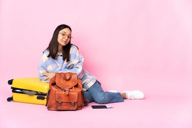 웃 고 바닥에 앉아 가방을 가진 여행자 여자