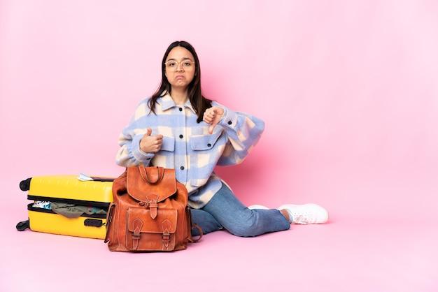 Женщина-путешественница с чемоданом сидит на полу, делая знак