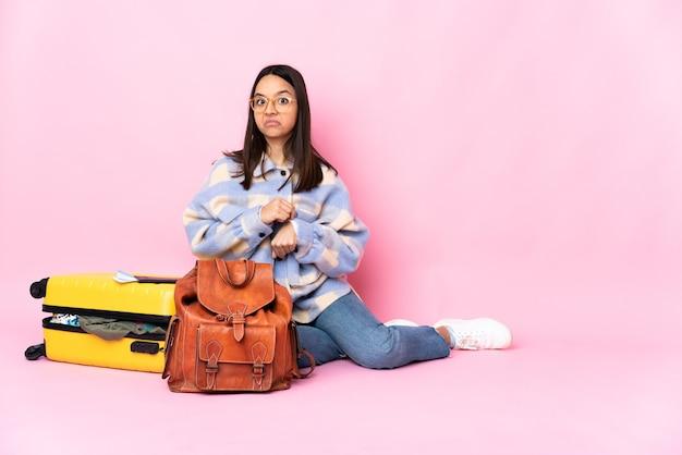 遅刻のジェスチャーをしている床に座っているスーツケースを持つ旅行者の女性