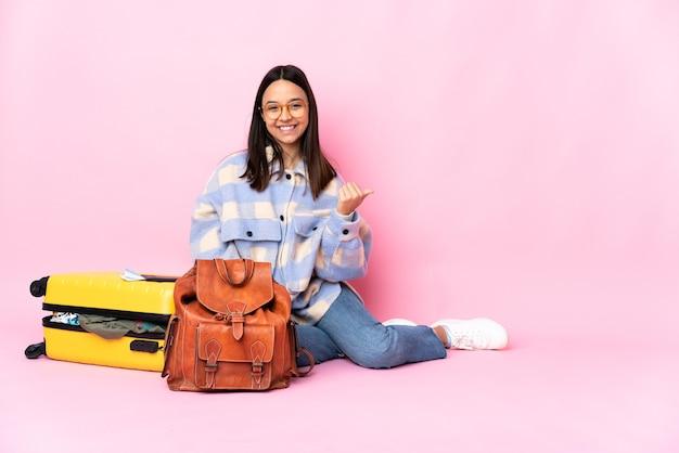 제품을 제시하기 위해 측면을 가리키는 바닥에 앉아 가방을 가진 여행자 여자