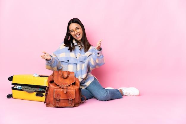 제시하고 손으로 초대하는 바닥에 앉아 가방을 가진 여행자 여자