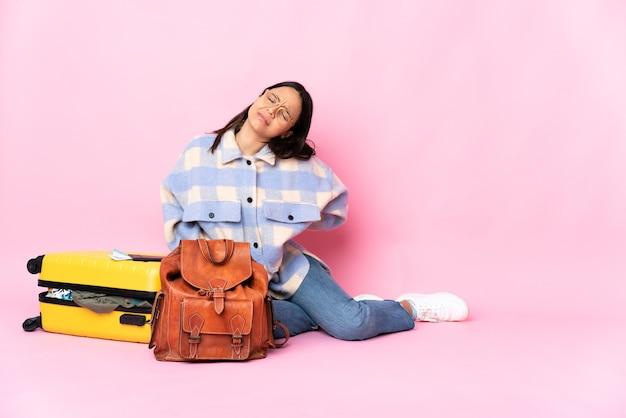 노력한 데 대한 요통으로 고통받는 바닥에 앉아 가방을 가진 여행자 여자