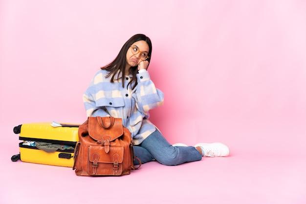 Женщина-путешественница с чемоданом сидит на полу с усталым и скучающим выражением лица