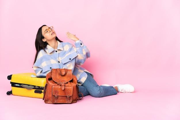 Женщина-путешественница с чемоданом сидит на полу с усталым и больным выражением лица