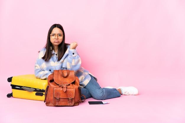 불행한 표정으로 바닥에 앉아 가방을 가진 여행자 여자