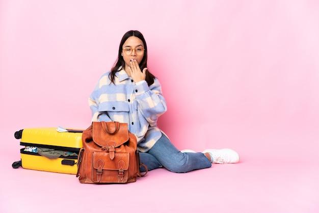 Женщина-путешественница с чемоданом сидит на полу, зевая и прикрывая рукой широко открытый рот