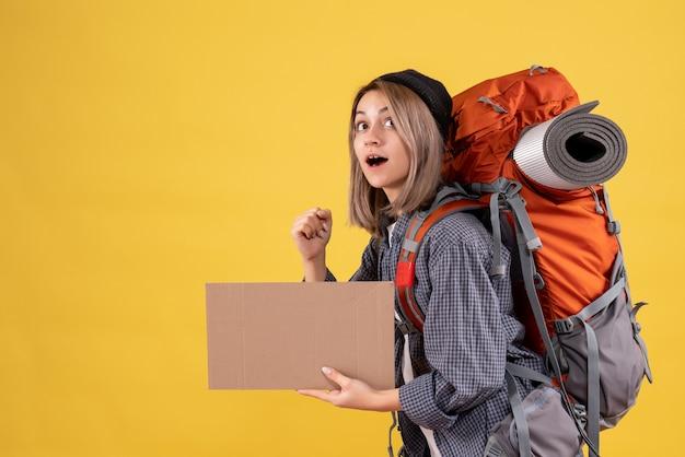 Donna viaggiatrice con zaino che tiene cartone in fretta