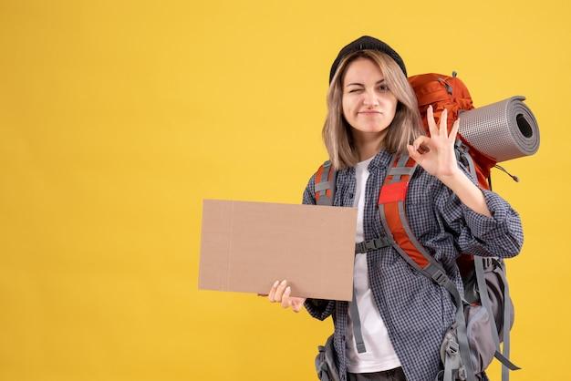 Donna viaggiatrice con zaino in possesso di cartone che fa segno ok
