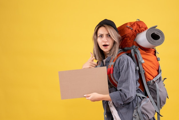Donna viaggiatrice con zaino che tiene cartone rivolto verso la telecamera