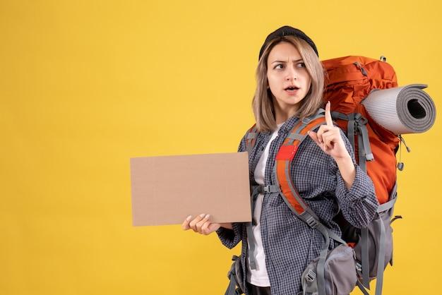 Donna viaggiatrice con zaino in possesso di cartone che punta il dito in su