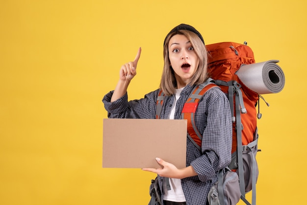 Traveler woman with backpack holding cardboard pointing with finger up