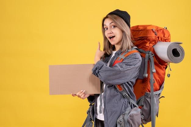 Donna viaggiatrice con zaino che tiene in mano un cartone che punta dietro