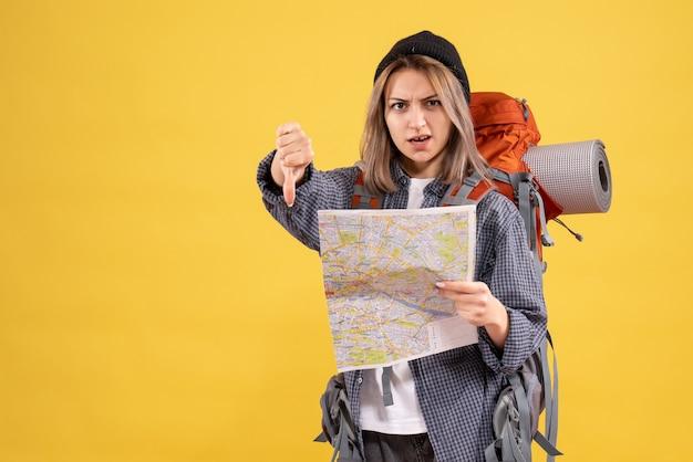 Путешественница женщина с рюкзаком держит карту, показывая палец вниз