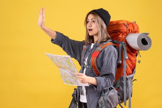 Donna viaggiatrice con lo zaino che tiene la mappa che saluta qualcuno