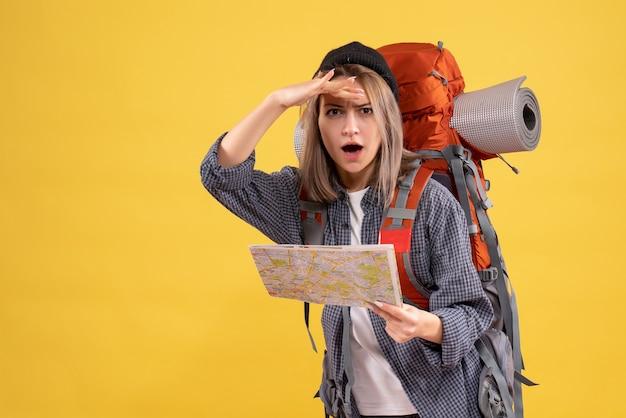 カメラ目線の地図を持ったバックパックを持つ旅行者の女性