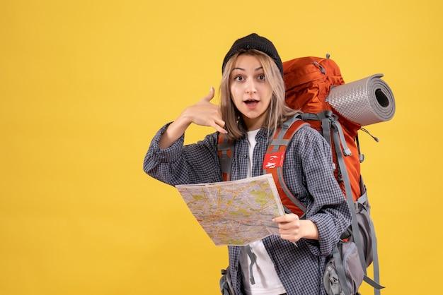 地図を持ってバックパックを持つ旅行者の女性がサインを呼んでくれます