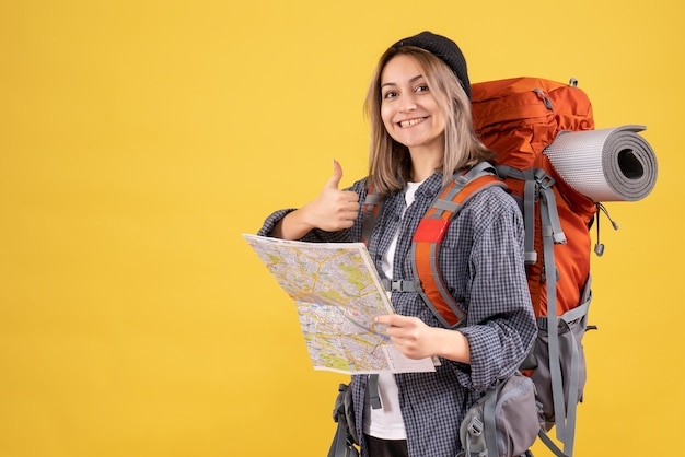 Donna viaggiatrice con lo zaino che tiene la mappa che fa il segno del pollice in su