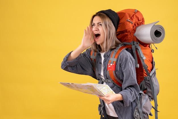 叫んでいる地図を持ったバックパックを持つ旅行者の女性