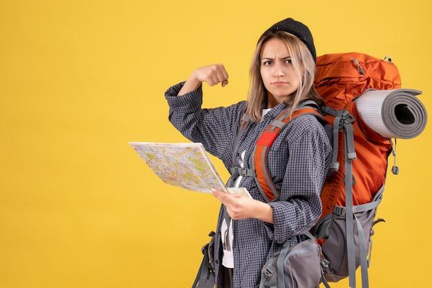 腕の筋肉を示す地図を持ったバックパックを持つ旅行者の女性