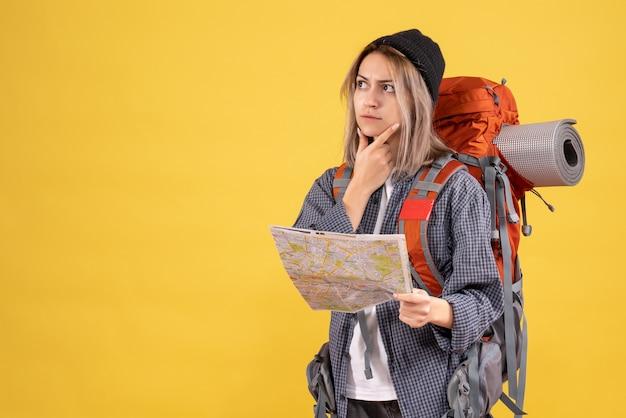 彼女の旅について考えて地図を持ったバックパックを持つ旅行者の女性