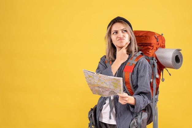 Женщина-путешественница с рюкзаком держит карту, думая о путешествии