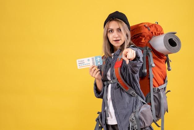 Donna viaggiatrice con lo zaino che tiene il biglietto puntato davanti