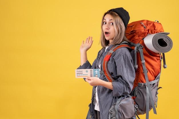 Donna viaggiatrice con zaino in possesso di biglietto che mostra