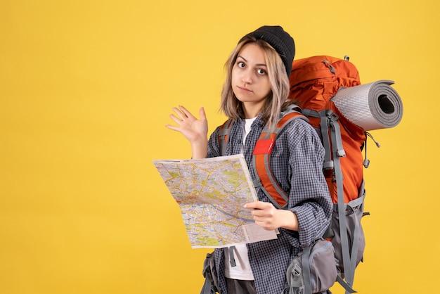 黄色の地図を持ってバックパックを持つ旅行者の女性