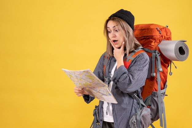 大きな驚きで地図を見ているバックパックを持つ旅行者の女性