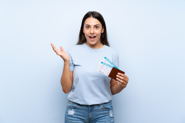 Traveler woman with boarding pass over isolated blue wall with shocked facial expression