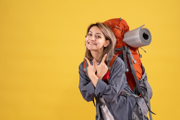Donna viaggiatrice con un sorriso luminoso che indossa uno zaino rosso