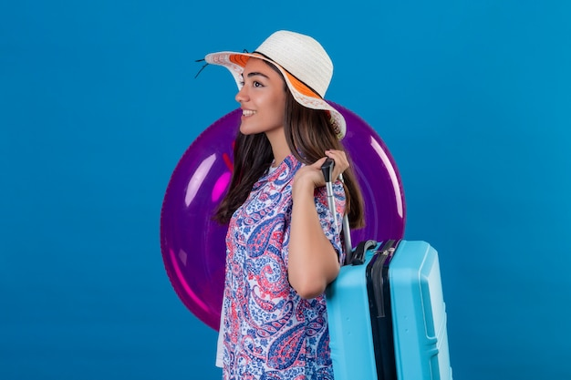 Traveler woman with hat standing with inflatable ring and traveler suitcase happy smiling ready to holiday on isolated blue