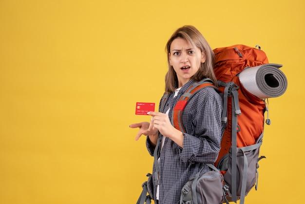 Donna viaggiatrice con carta in possesso di zaino rosso