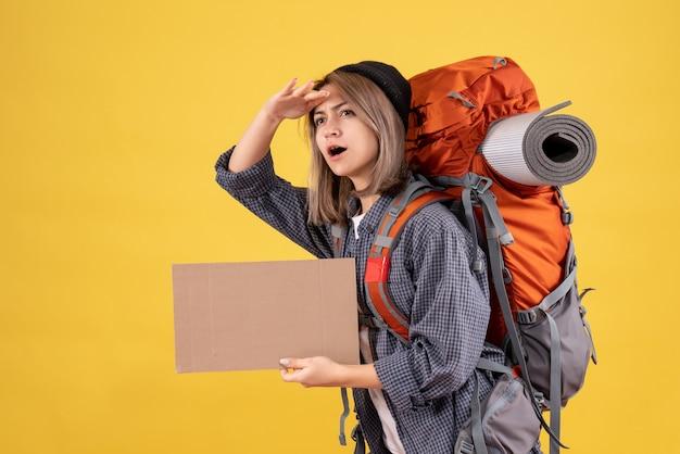 Donna viaggiatrice con zaino rosso che tiene cartone