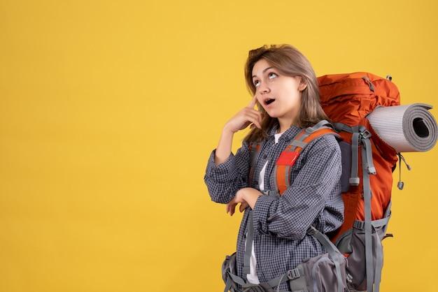 Donna viaggiatrice con zaino rosso che pensa al viaggio
