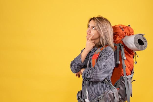 Donna viaggiatrice con zaino rosso pensando